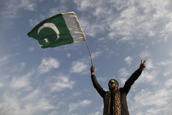 A supporter of Dr Qadri waves a Pakistan flag as he takes part in the second day of a protest in Islamabad