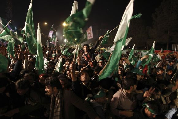 Supporters of Dr Qadri wave Pakistani flags during a protest in Islamabad on Tuesday