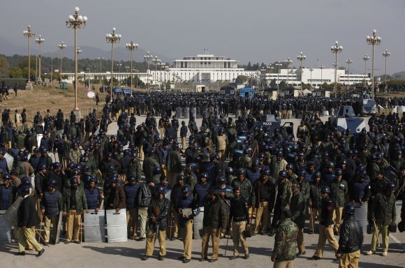 Riot police officers gather outside parliament during second day of protest by supporters Dr Qadri in Islamabad