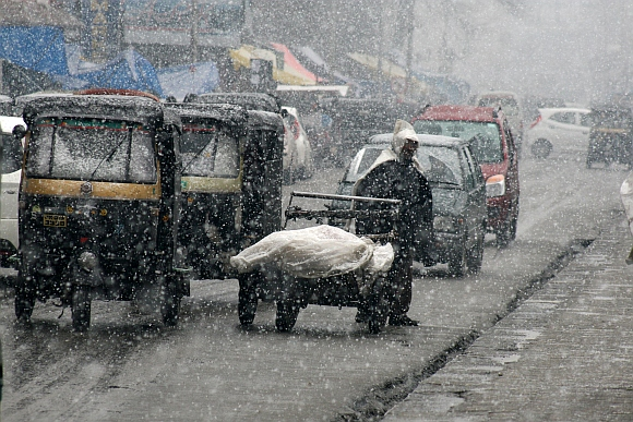 Vehicles ply on roads during the snowfall in srinagar