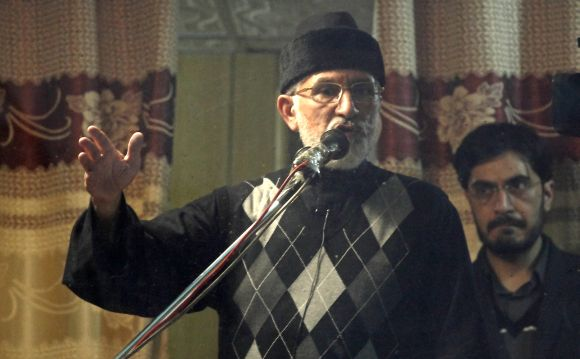 Dr Tahir-ul Qadri addresses his supporters behind the window of an armoured vehicle in Islamabad