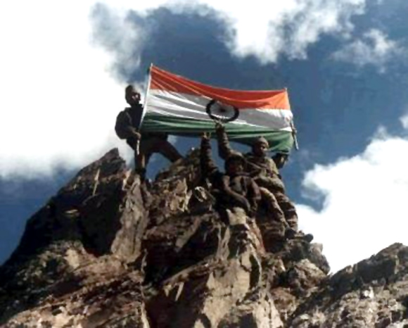 Indian soldiers hoist the tricolour atop a recaptured peak during the Kargil war.