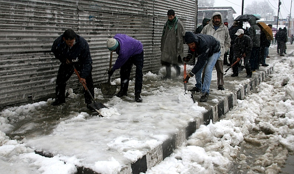 Workers clear footpaths after the heavy snowfall