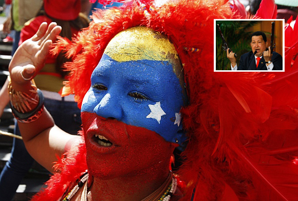 A supporter of Venezuelan President Hugo Chavez (inset) with her face painted in the colours of the national flag, attends a rally in Caracas
