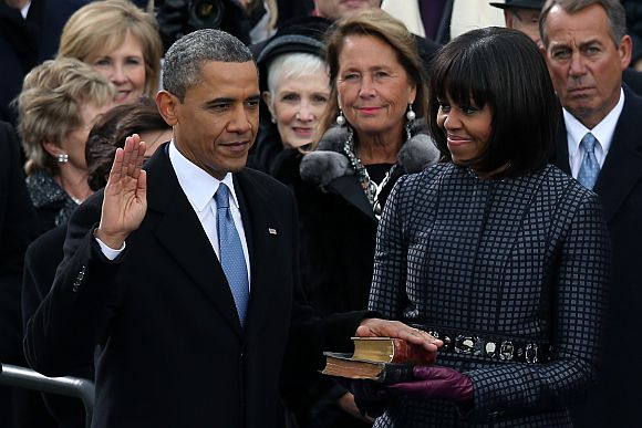 US President Barack Obama is sworn in during the public ceremony as First lady Michelle Obama looks on during the presidential inauguration on the West Front of the US Capitol January 21 in Washington, DC