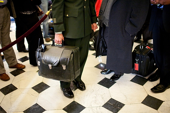 A military aide carries the nuclear football, with the nation's nuclear launch codes, through Statuary Hall as President Barack Obama arrives at the US Capitol for his address to a joint session of Congress on February 24, 2009 in Washington