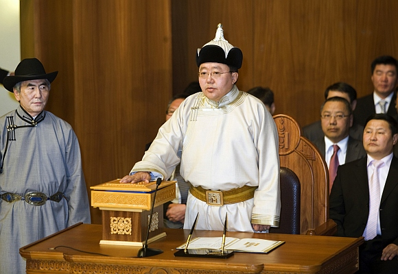 Mongolia's President Tsakhiagiin Elbegdorj places his hand on the Constitutions as he takes an oath during the inauguration ceremony in Ulan Bator, Mongolia June 18, 2009