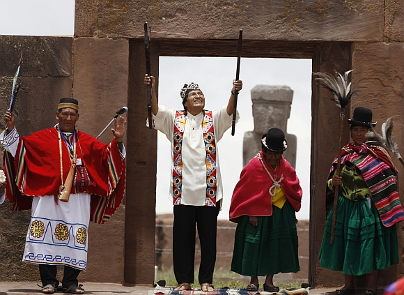 Bolivian re-elect President Evo Morales (second from left), accompanied by indigenous leaders, holds the staff of command during an Aymara indigenous ceremony at Tiwanaku
