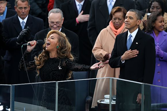 Singer Beyonce performs the national anthem as Obama looks on