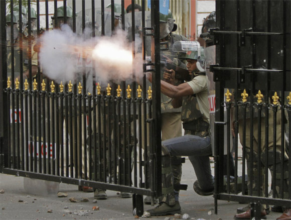 Riot police personnel fire tear gas towards pro-Telangana supporters