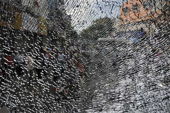 A broken window pane of a passenger bus is pictured after it was damaged by activists demanding a separate Telangana state