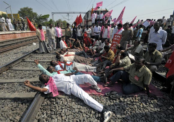 Pro-Telangana supporters shout slogans as they block the way of a passenger train during a protest at a railway station in Hyderabad