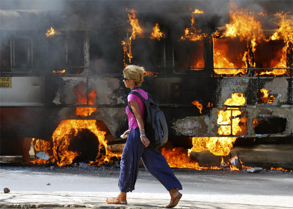 A foreign student of Osmania University walks past a bus set ablaze by pro-Telangana supporters