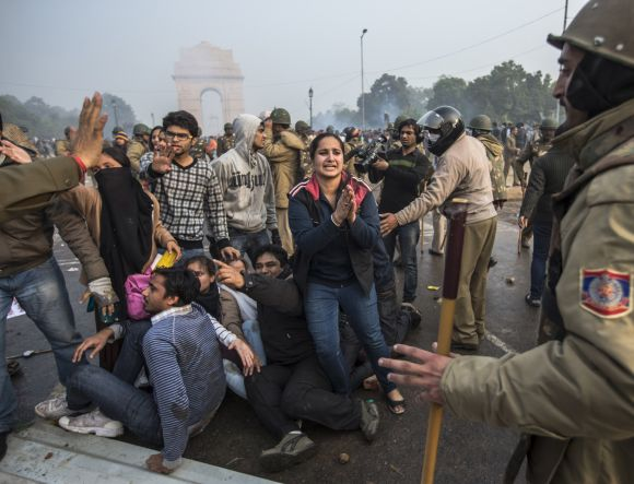 A protestor begs for mercy as Delhi police lathi charge during a protest