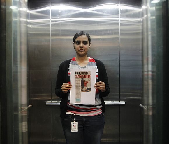 Deepshikha poses inside her office elevator holding a notice that reads 'sorry I am not staying late now' in her office in Gurgaon on the outskirts of New Delhi