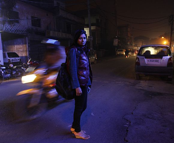 Sheetal, 23, who works at a night call centre, poses for a photograph