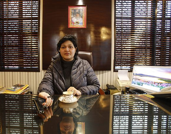 Nalini Bharatwaj, 37, chairman of a management institute, holds a gun while posing in her office in New Delhi