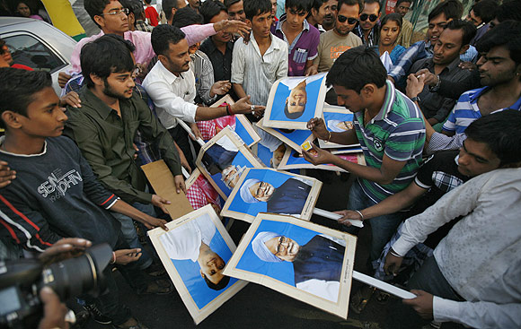 Demonstrators prepare to burn portraits of India's PM Singh and lawmaker Rahul Gandhi during a protest in Ahmedabad