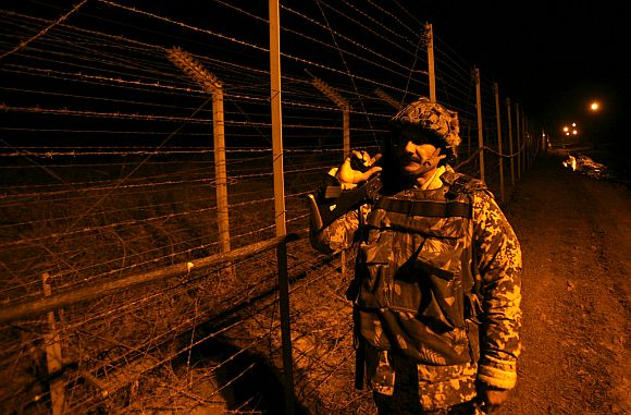 A Border Security Force trooper near the fenced border with Pakistan in Suchetgarh, Jammu and Kashmir