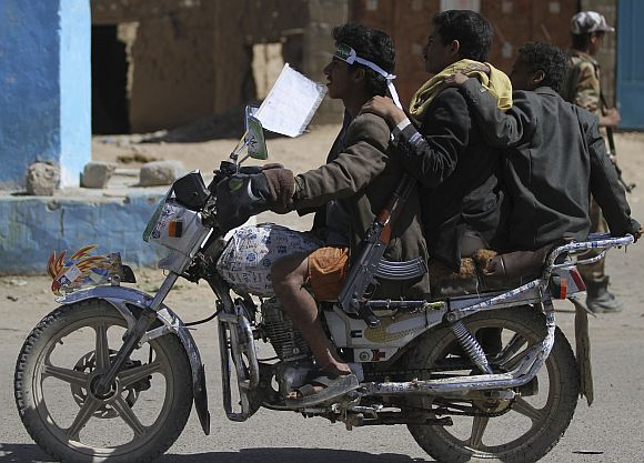 Followers of Yemen's al-Houthi Shi'ite group ride a motorcycle while carrying weapons, in the northwestern province of Saada