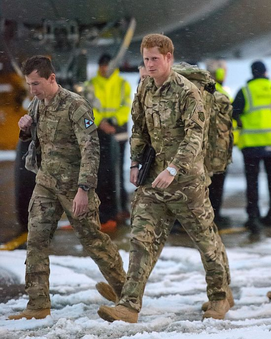 Britain's Prince Harry (R) walks after disembarking from a Voyager transport aircraft at RAF Brize Norton, southern England January 23