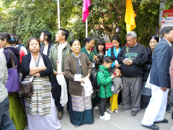 People wait for the Dalai Lama with roses
