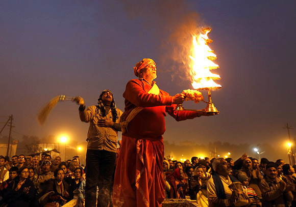 A Hindu priest performs evening prayers near the banks of the Ganga in Allahabad.