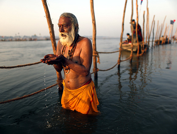 A devotee prays before taking a dip in the waters of the Ganga