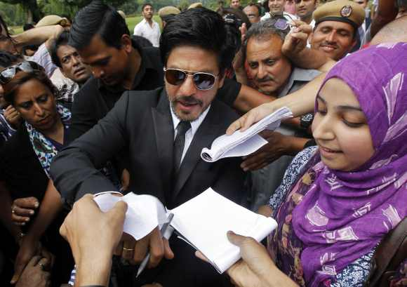 A fan gets an autograph from Khan