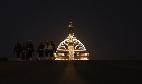Members of the military band walk in front of the illuminated Presidential Palace after the ceremony in New Delhi