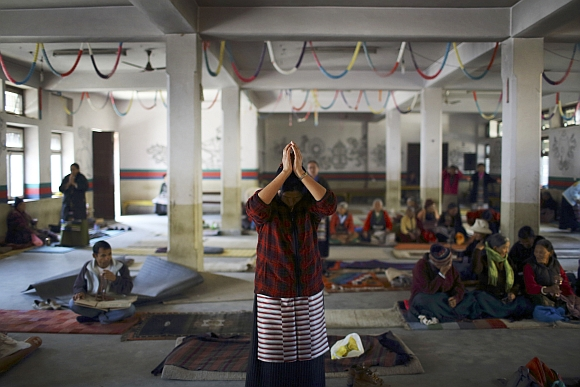 A Tibetan woman offers prayer upon her arrival during an event organised to express solidarity with the victims of violence in Tibet