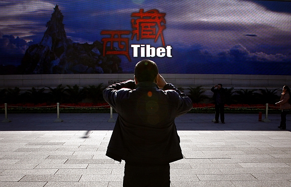 A man takes a photograph in front of a screen displaying propaganda about China's Tibet Autonomous Region on Beijing's Tiananmen Square