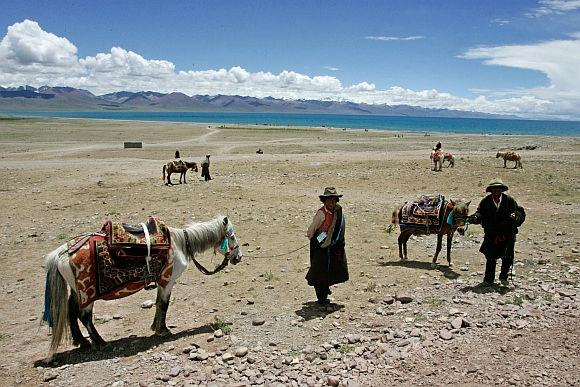 Tibetan nomads wait for tourists to ride their horses at Namtso Lake in Tibet Autonomous Region