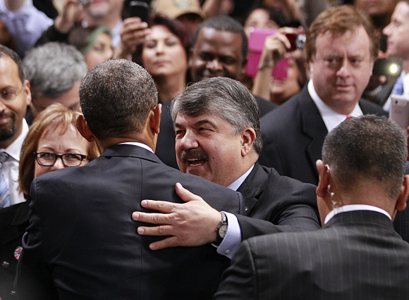 Obama is hugged in the audience by Richard Trumka, president of the AFL-CIO union organisation, after the remarks