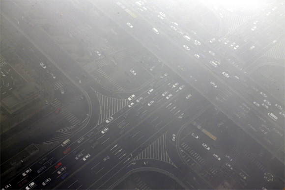 Cars drive through Guomao bridge on a hazy day in Beijing's central business district