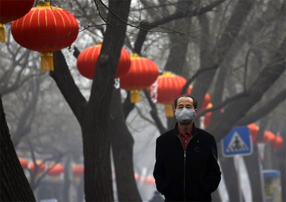 A man wearing a mask walks along a street in central Beijing