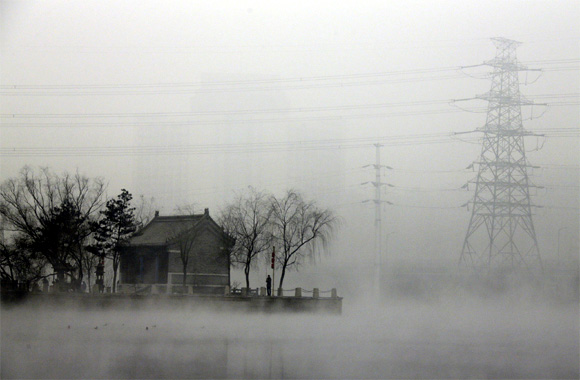 A man fishes near a temple on a hazy day during winter in Beijing's Gaobeidian village