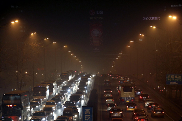 Cars drive along east 3rd Ring Road on a foggy evening in Beijing