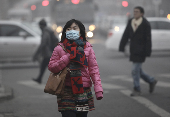 A woman wearing a mask walks along a street on a hazy day in Beijing