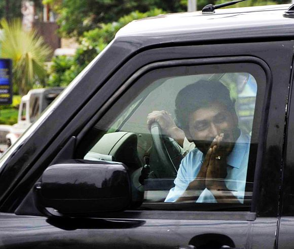 Jailed YSR Congress chief Jaganmohan Reddy greets his supporters as he arrives at the CBI office in Hyderabad