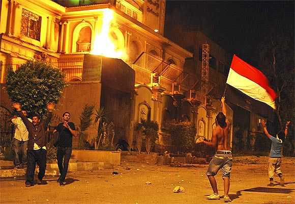 Protesters opposing Mursi wave Egyptian flag and shout slogans against him and members of the Muslim Brotherhood after attacking the national headquarters of the Muslim Brotherhood with Molotov cocktails in Cairo