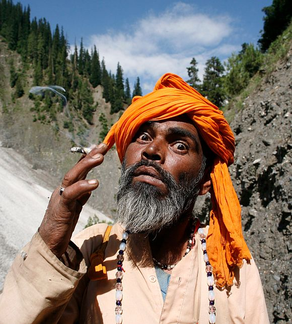 A sadhu smokes while on his way to the cave shrine