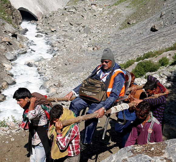Porters carrying a pilgrim to the cave shrine