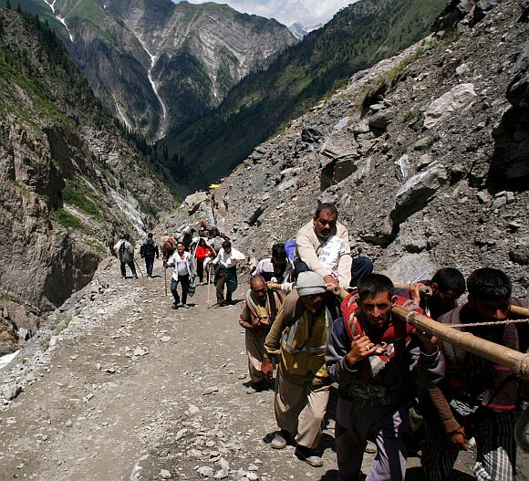 Porters carrying pilgrims to the cave shrine