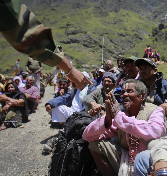 A survivor pleads with a soldier to allow him to board an army helicopter, during rescue operations at Badrinath