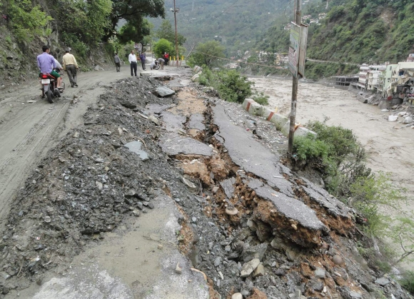 People walk along road that was damaged due to the floods in Uttarakhand