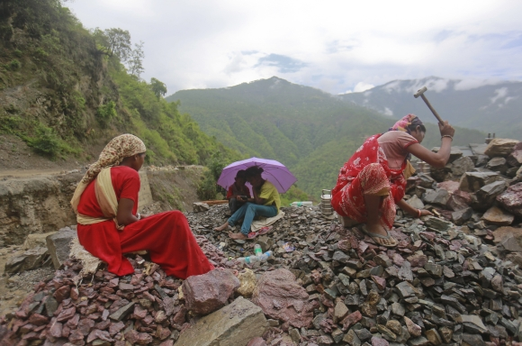 Workers repair a road damaged by a landslide, which was caused by heavy rainfall in Chamba, Uttarakhand