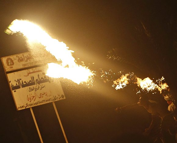 A protester opposing Egyptian President Mohamed Mursi throws Molotov cocktails at the national headquarters of the Muslim Brotherhood in Cairo's Moqattam district