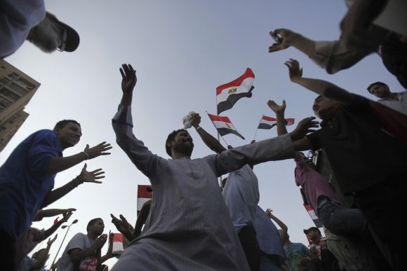 Protesters, who are against Morsi, dance and react in front of the Republican Guard headquarters in Cairo