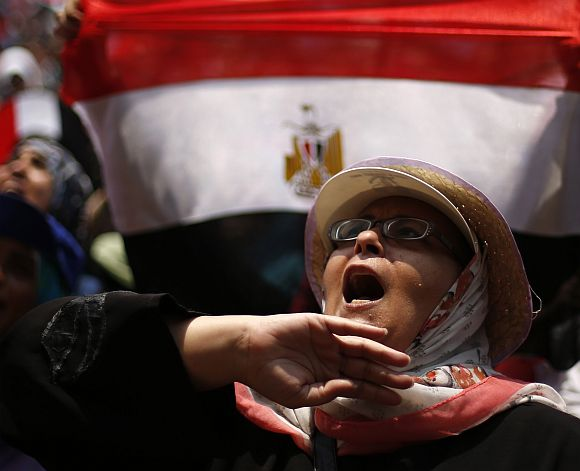 A protester, who is against Egyptian President Mohamed Mursi, shouts as she demonstrates in Tahrir Square in Cairo
